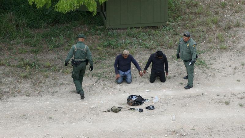 Border patrol agents apprehend people who illegally crossed the border from Mexico into the US [Loren Elliot/Reuters]