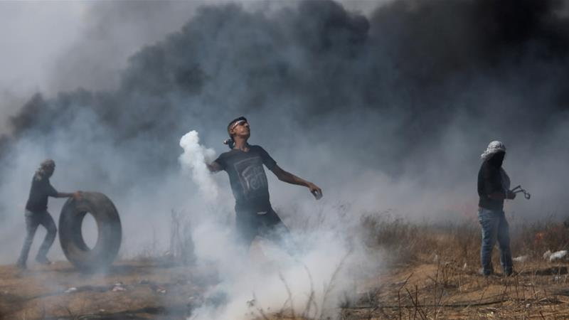 A demonstrator hurls back a tear gas canister fired by Israeli troops during a protest at the Israel-Gaza border [Ibraheem Abu Mustafa/Reuters]