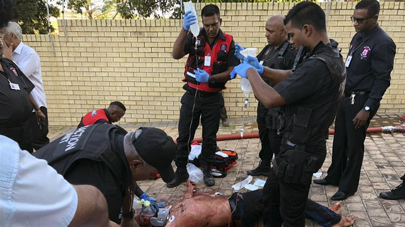 Paramedics attend to a wounded man after attackers entered a mosque in Verulam on Thursday [South African Police Services via AP]