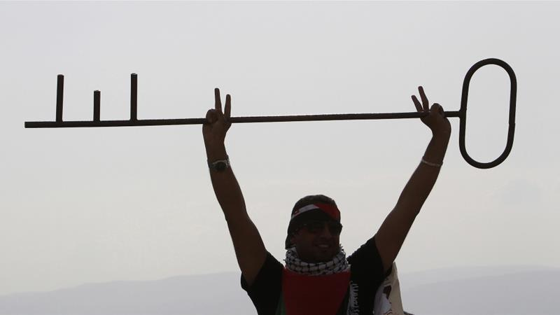 A Palestinian refugee holds a giant key to symbolise the right of return of refugees during a demonstration to mark the anniversary of Nakba [Muhammad Hamed/Reuters]