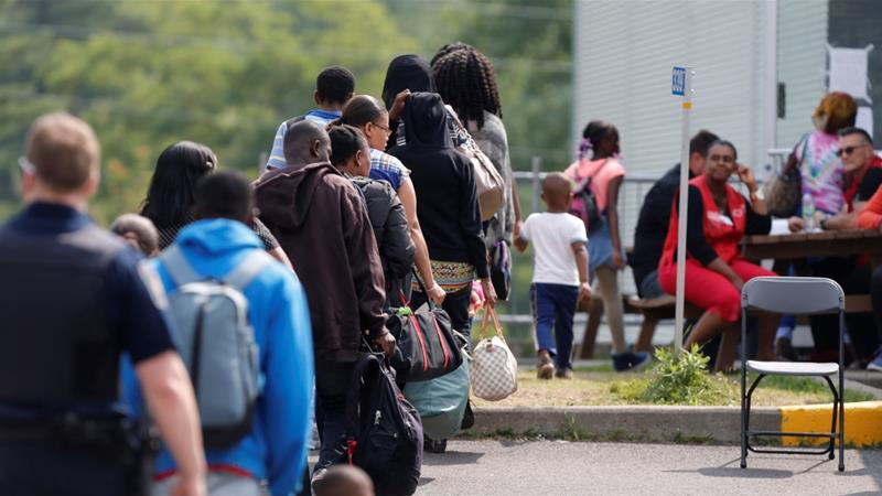 Asylum seekers wait to be processed after being escorted from their tent encampment to Canada Border Services officials [Reuters]