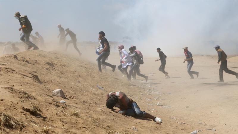 Palestinian demonstrators run from tear gas fired by Israeli forces during a protest marking the 70th anniversary of the Nakba in the southern Gaza Strip [Ibraheem Abu Mustafa/Reuters]
