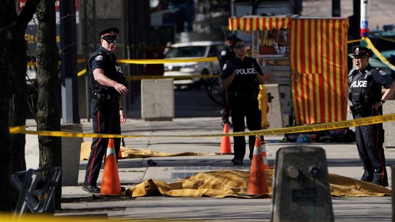 Police officers stand near covered bodies after a van struck multiple people at a major intersection in Toronto [Carlo Allegri/Reuters]