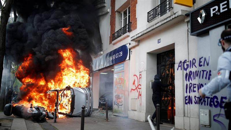 A car is on fire during clashes in the French capital [Christian Hartmann/Reuters]