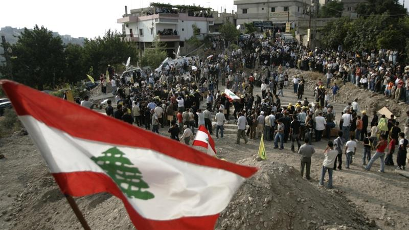 A Lebanese flag is seen as mourners bury 29 Lebanese victims - mostly women and children - of an Israeli attack in the Lebanese village of Qana, on August 18, 2006 [AP Photo/Lefteris Pitarakis]