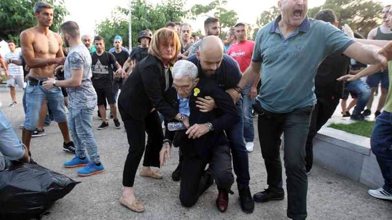 Mayor of Thessaloniki, Yiannis Boutaris is aided after being attacked by a group of nationalists during a Sunday commemoration of what is known as the genocide of the Pontians, on 19 May 2018 [EPA]