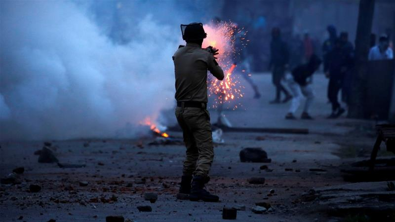 An Indian police officer fires a tear gas shell towards demonstrators, during a protest against the recent killings in Kashmir, in Srinagar May 8, 2018 [Danish Ismail/Reuters]