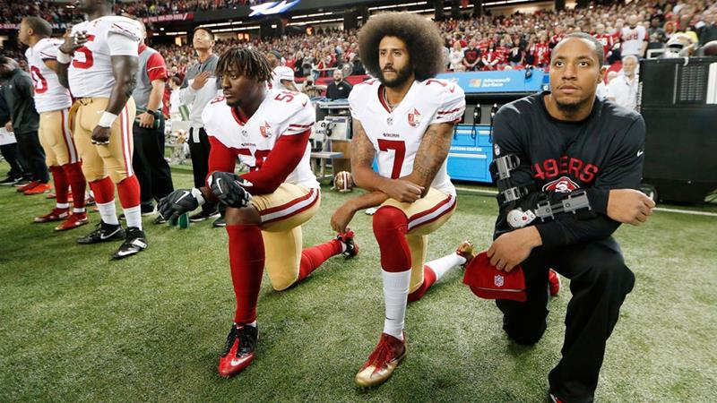 In this Dec 18, 2016, file photo, San Francisco 49ers quarterback Colin Kaepernick kneels during the playing of the national anthem before an NFL football game [John Bazemore/AP]