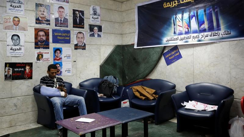 "A journalist sits beside pictures of fellow journalists who have been arrested and a banner that reads ""The press, It is not a crime"" during World Press Freedom Day in Cairo [Amr Abdallah Dalsh/Reuters]"