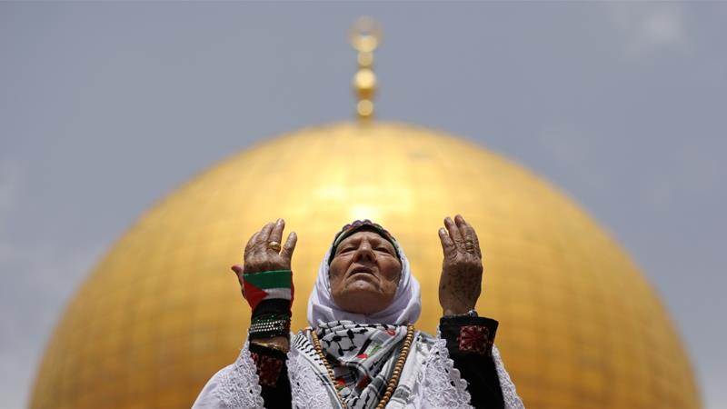 The Dome of the Rock is seen in the background as a Palestinian woman prays on the second Friday of the holy fasting month of Ramadan, in Jerusalem's Old City, May 25, 2018 [Ammar Awad/Reuters]