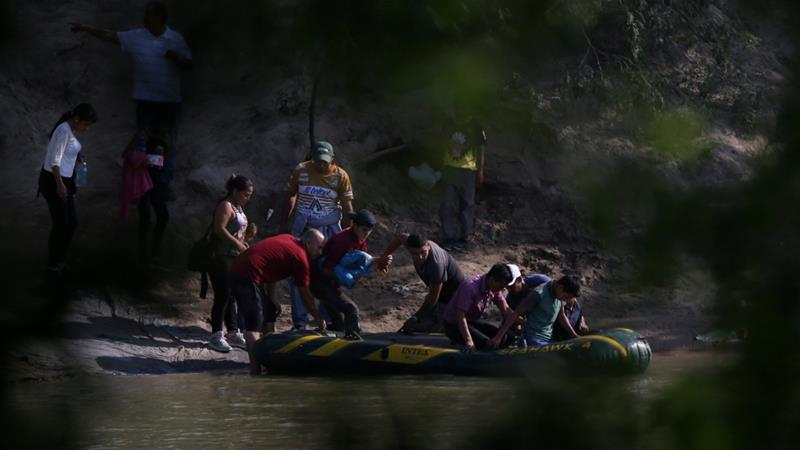 Migrants preparing to cross into the US from Mexico [Loren Elliott/Reuters]