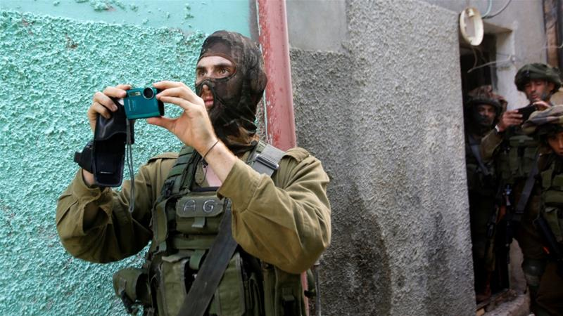 An Israeli army soldier films during a searching raid in the West Bank al Fawwar refugee camp south of Hebron