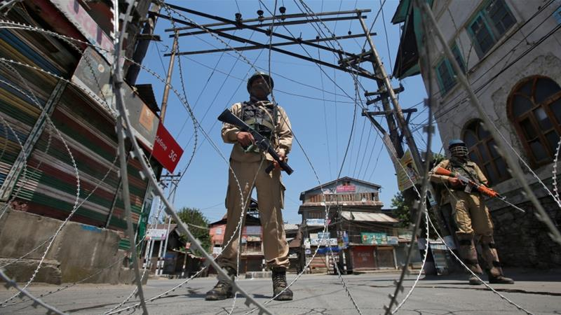 Indian policemen stand guard behind wire during a strike called by separatists in Srinagar [Danish Ismail/Reuters]