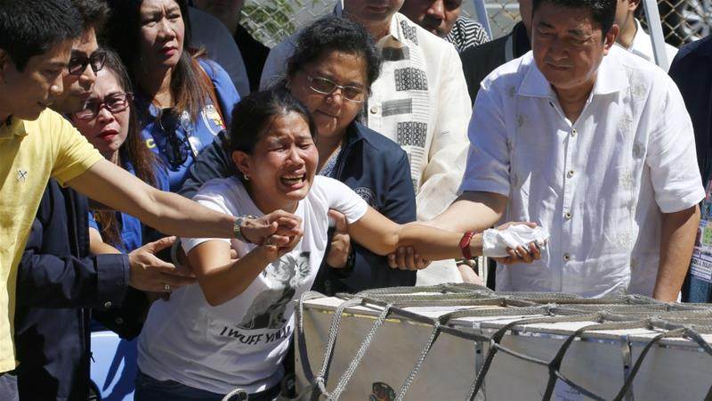 Relatives of Joanna Demafelis, whose corpse was found in a freezer in Kuwait, react as her coffin arrives at the Ninoy Aquino International Airport in Manila on February 16 [File: AP/Bullit Marquez]
