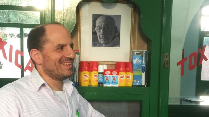 Yousef Geday, of El-Kamal Pharmacy, stands next to a photo of his late father Fakhri in al-Ajami, Jaffa [Linah Alsaafin/ Al Jazeera]