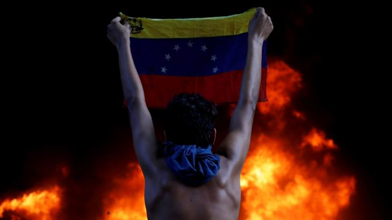 A protester holds a national flag while standing in front of a fire burning during a rally against Venezuela's President Nicolas Maduro, in Caracas [Carlos Garcia Rawlins/Reuters]
