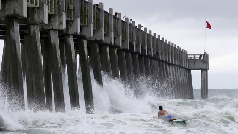 A surfer makes his way out into the water as a subtropical storm approaches on Monday [Dan Anderson/AP]