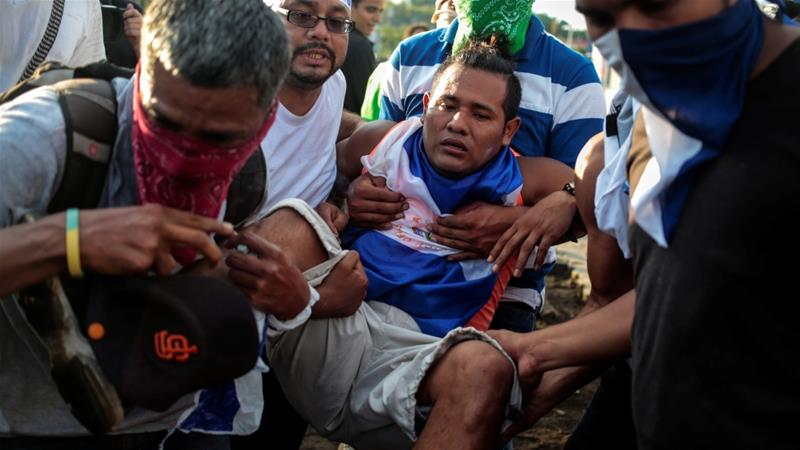Demonstrators help an injured protester during clashes with riot police during a protest against President Daniel Ortega's government in Managua, Nicaragua on May 30, 2018 [Oswaldo Rivas/Reuters]