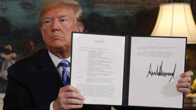 Trump displays a presidential memorandum after announcing his intention to withdraw from the deal [Jonathan Ernst/Reuters]