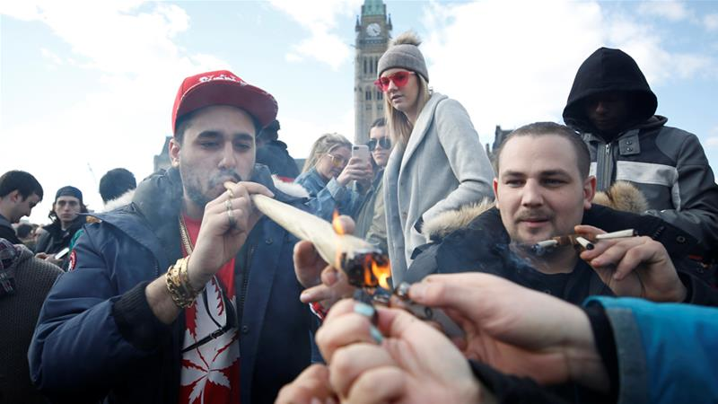 A man smokes a large joint during the annual 4/20 marijuana rally on Parliament Hill in Ottawa last month [Chris Wattie/Reuters]