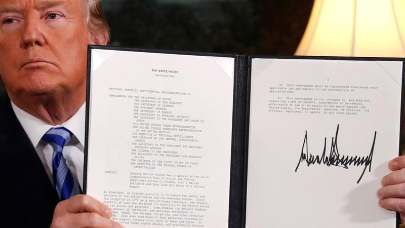 President Donald Trump holds up a proclamation declaring his intention to withdraw from the JCPOA after signing it in the Diplomatic Room at the White House