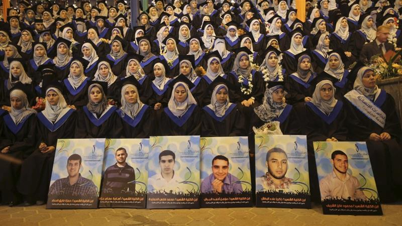 Palestinian graduates sit behind posters of fellow students who were killed in an Israeli offensive at a graduation ceremony at the University College of Applied Sciences in Gaza in 2014 [Reuters]