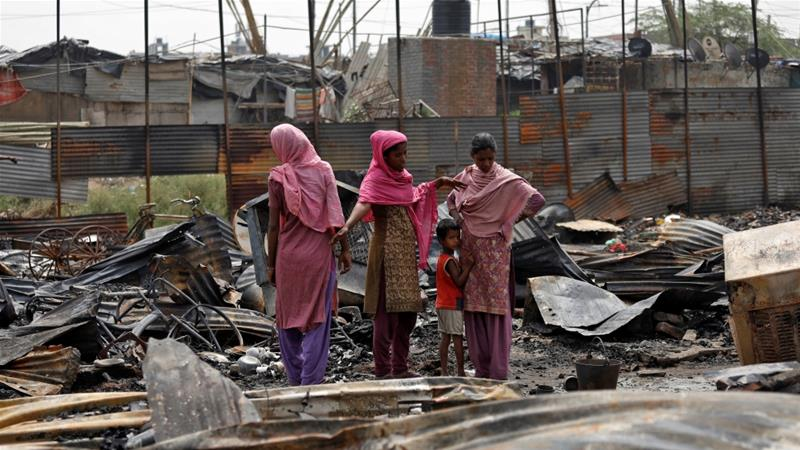 Rohingya women stand on the ruins of dwelling destroyed in a fire at a camp in Bangladesh [Saumya Khandelwal/Reuters]
