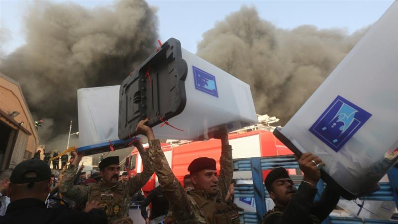 Security forces carry ballot boxes as smoke rises from the storage site in Baghdad [Reuters]