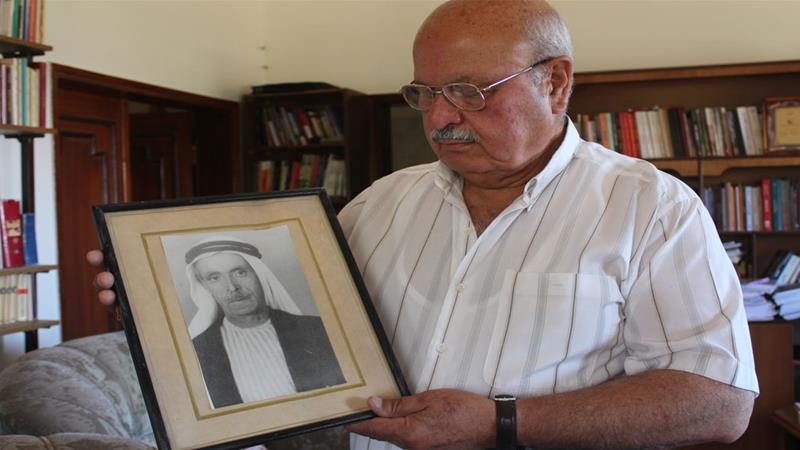 Abdel-Majeed Hamdan holds up a photo of his father, Mustafa, whose body was never recovered after he was killed by Israeli forces while crossing the Jordan River in 1967 [Shatha Hammad/Al Jazeera]