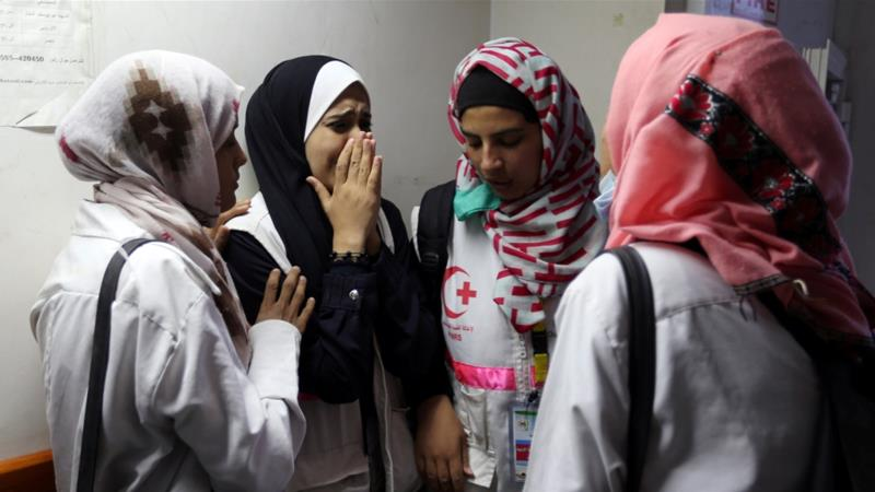 Colleagues of Palestinian nurse Razan Al-Najjar cry at the news that she was killed during a protest at the Israel-Gaza border on June 1, 2018  [Reuters/Ibraheem Abu Mustafa]