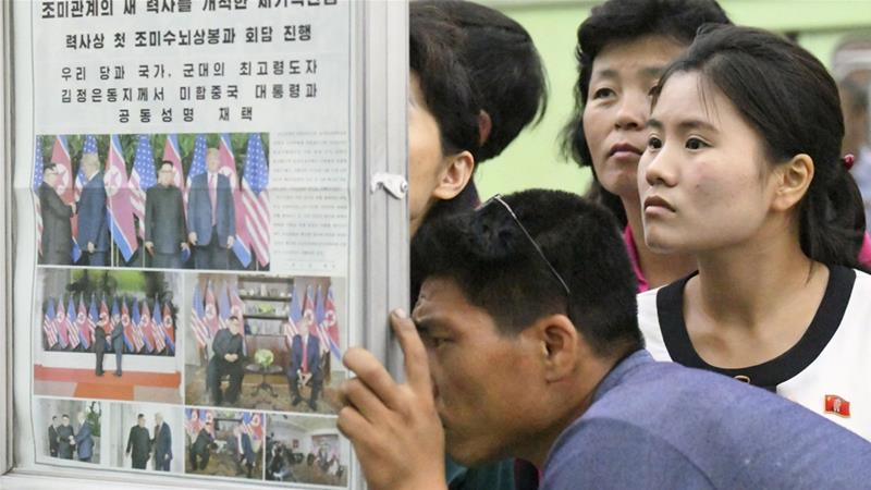 North Koreans watched the displayed local newspapers reporting the Singapore summit on June 13 [Kyodo/Reuters]