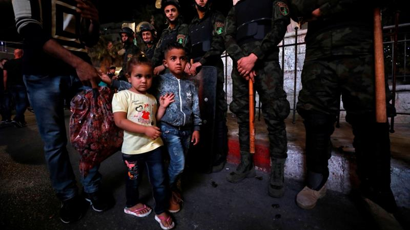Security forces carrying batons stand guard as children walk during a protest calling on the PA to lift its sanctions against Gaza, in Ramallah, on June 13, 2018 [Mohamad Torokman/Reuters]