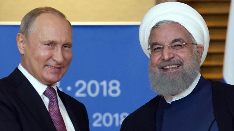 Russian President Vladimir Putin and Iranian President Hassan Rouhani pose for a photo during their meeting in Qingdao, China, on June 9, 2018 [AP/Alexander Zemlianichenko]