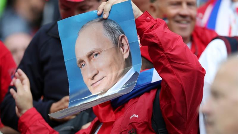 Serbia fan holds up a photo of Russian President Vladimir Putin before the Serbia vs Switzerland match at Kaliningrad Stadium on June 22, 2018 [Reuters/Mariana Bazo]