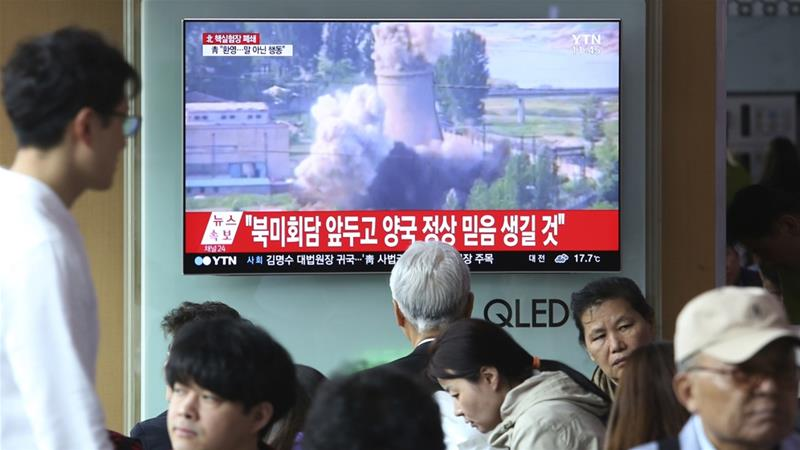 A TV screen shows file footage of the demolition of a cooling tower at North Korea's main reactor complex in Yongbyon in 2008 [File: AP]