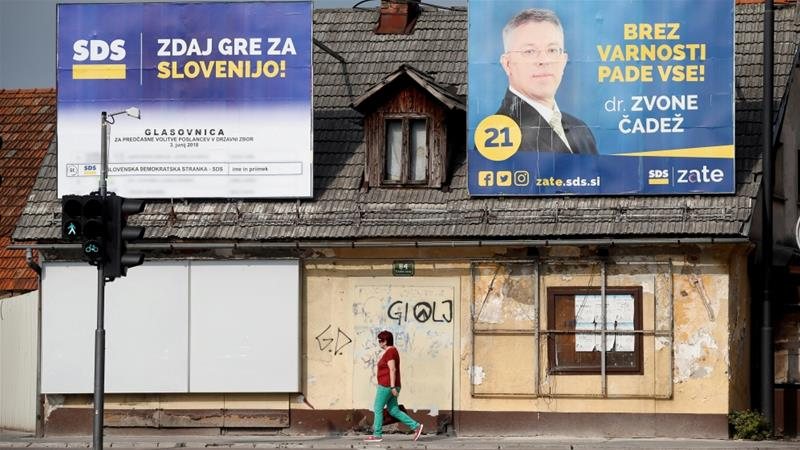 A woman walks under election posters of the SDS party for general elections in Ljubljana [Borut Zivulovic/Reuters]