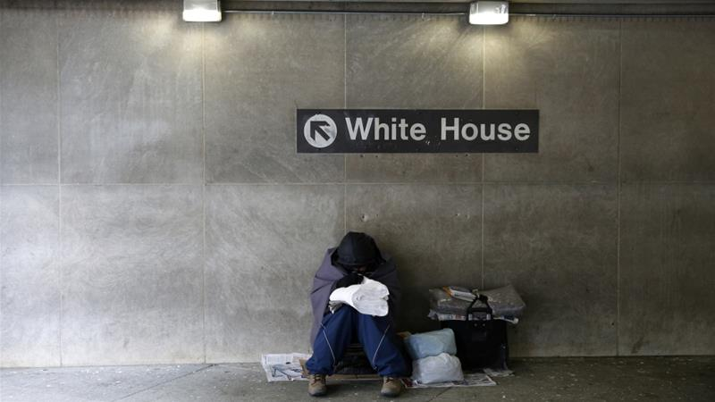 On a cold winter's day, a homeless person tries to stay warm at the entrance of a subway station near the White House in Washington, DC, US [Kevin Lamarque/Reuters]