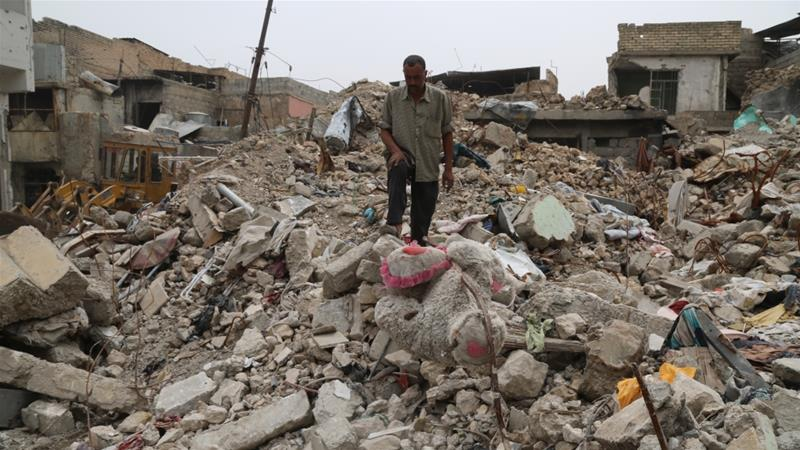 Destroyed buildings are seen in Mosul, which was retaken from ISIL fighters a year ago [Reuters]