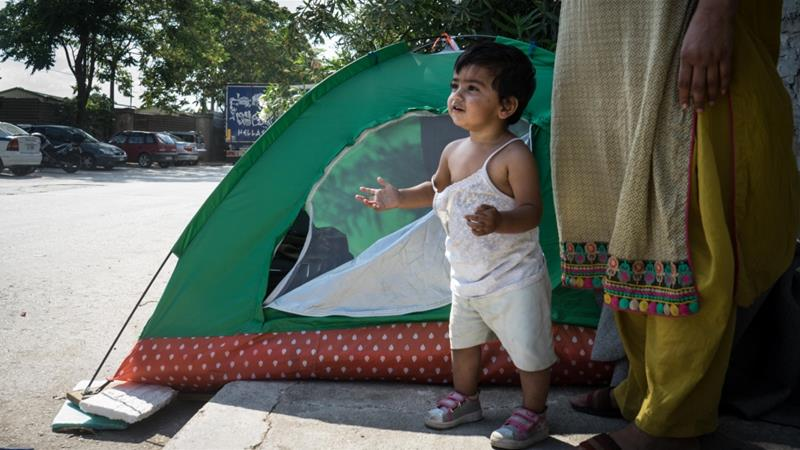 Manazza Fatima's 16-month-old daughter stands outside the cramped tent where they live outside a refugee camp [Patrick Strickland/Al Jazeera]
