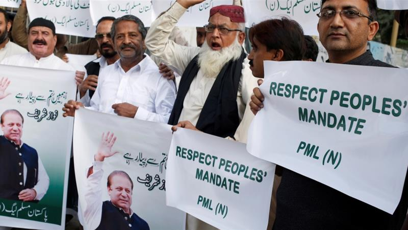 Supporters of ruling PML-N hold signs as they protest Supreme Court's decision to not allow deposed PM Nawaz to lead his party, in Karachi, Pakistan on February 22, 2018 [Akhtar Soomro/Reuters]
