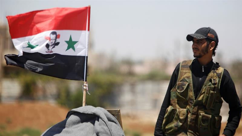 A Syrian soldier stands next to a Syrian flag in Umm al-Mayazen in the countryside of Deraa [Omar Sanadiki/Reuters]