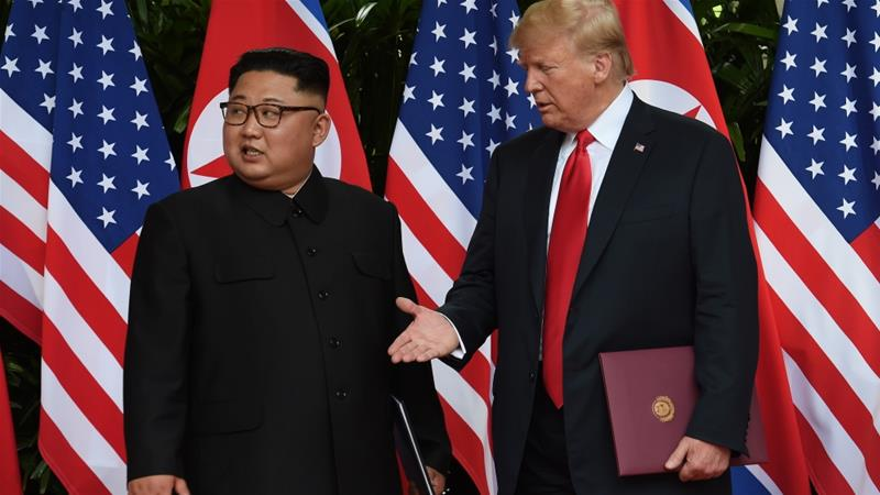 US President Donald Trump and North Korea's leader Kim Jong-un react during their summit at the Capella Hotel on Sentosa island in Singapore June 12, 2018 [Anthony Wallace/Pool via Reuters]