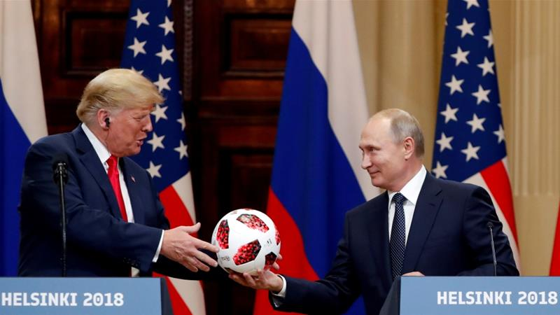 US President Donald Trump receives a football from Russian President Vladimir Putin as they hold a joint news conference after their meeting in Helsinki on July 16, 2018 [Reuters/Grigory Dukor]