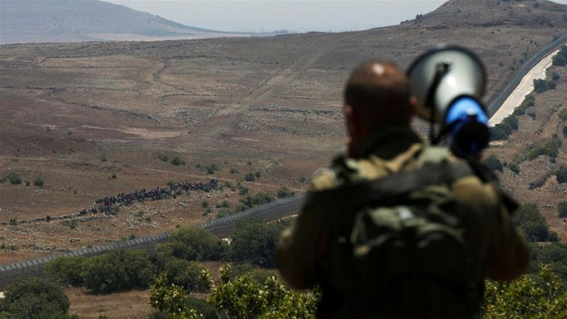 An Israeli soldier orders Syrians to leave the border at Israeli-occupied Golan Heights [Ronen Zvulun/Reuters]