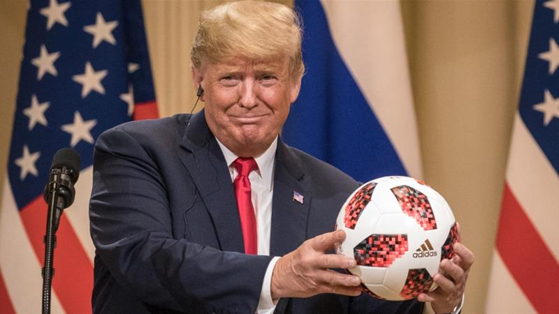 President Donald Trump shows off a football given to him by Russian President Vladimir Putin during a joint press conference after their summit on July 16 in Helsinki, Finland [Chris McGrath/Getty]