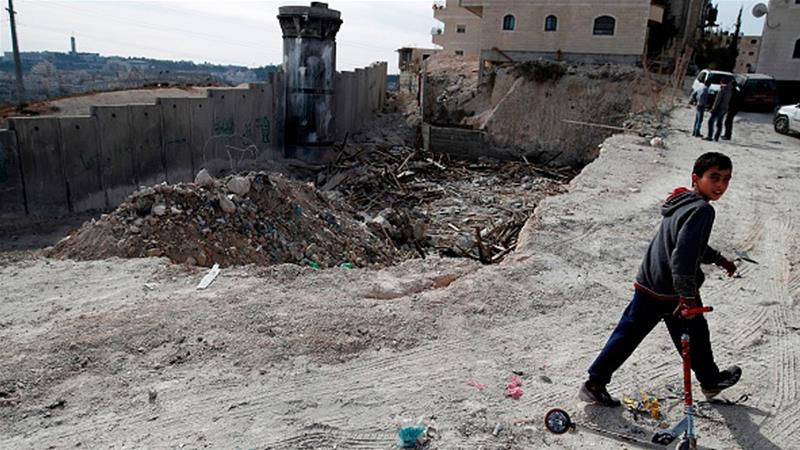 A Palestinian boy walks past the rubble of a demolished house in East Jerusalem [Ahmad Gharabli/AFP/Getty Images]