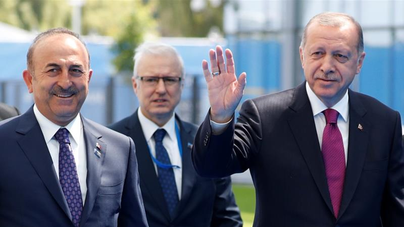 Turkish President Recep Tayyip Erdogan, right, and Foreign Minister Mevlut Cavusoglu, left, at the NATO summit in Brussels [Paul Hanna/Reuters]