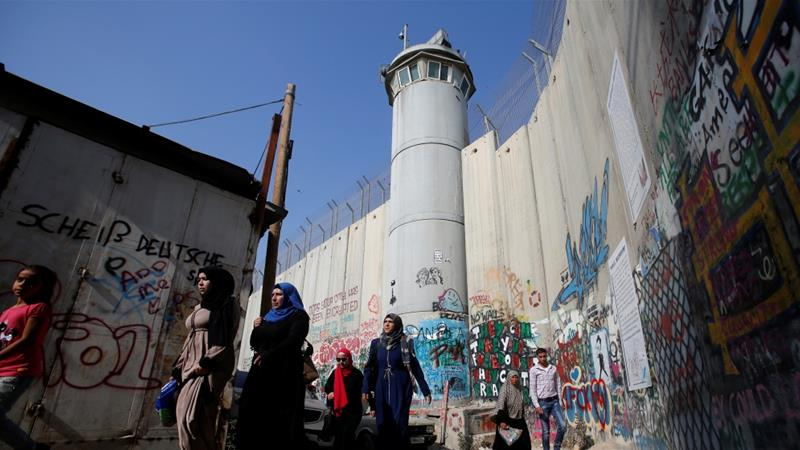 Palestinians pass by a section of the controversial Israeli barrier in Bethlehem in the occupied West Bank on their way to attend Friday prayer [File: Mussa Qawasma/Reuters]