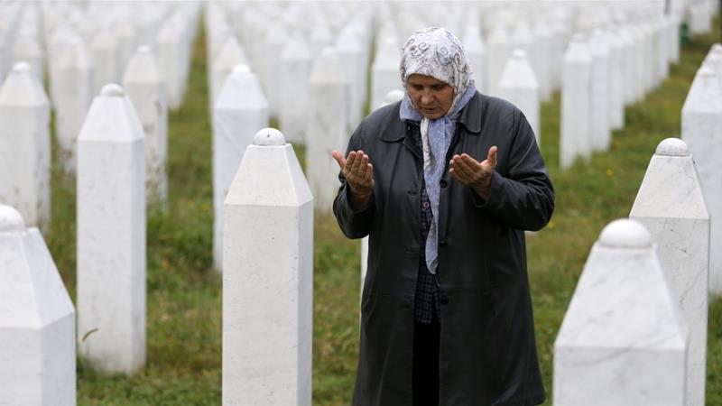 Hatidza Mehmedovic prays near the graves of her two sons and husband at a memorial near Srebrenica [Dado Ruvic/Reuters]