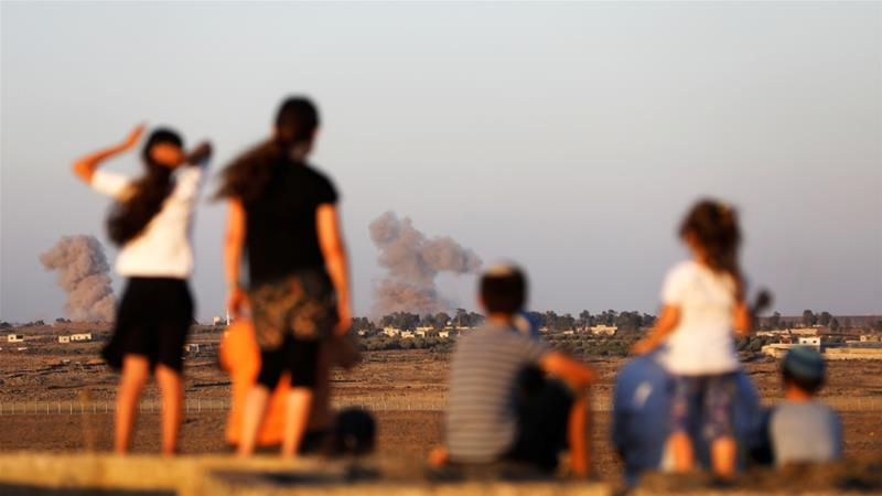 Israeli children watch as smoke rises from the Israeli-occupied Golan Heights [Ronen Zvulun/Reuters]